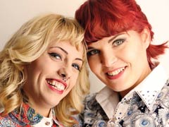 Two attractive Lesbian Match Maker members with colourful hair and quirky clothes smiling for camera
